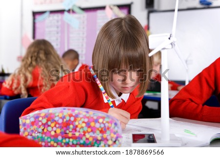 Serious middle school student sitting by desk in front of computer monitor Stock photo © pressmaster