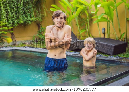 dad and son was frozen in the pool very cold water in the pool need heated water stock photo © galitskaya