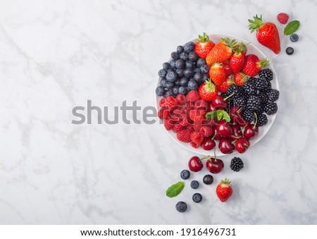 Fresh organic summer berries mix on white marble board on light kitchen table background. Raspberrie Stock photo © DenisMArt