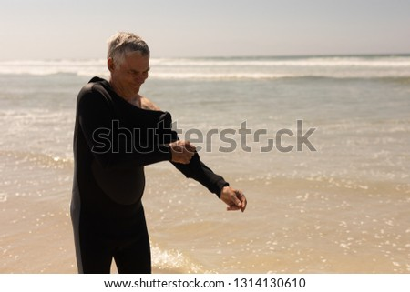 Side view of active senior male surfer wearing wet suit on the beach Stock photo © wavebreak_media