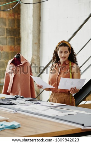 Young casual woman looking through new seasonal collection of clothes Stock photo © pressmaster