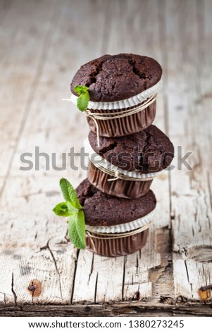 Chocolate dark muffins with mint leaves on rustic wooden table. Stock photo © marylooo