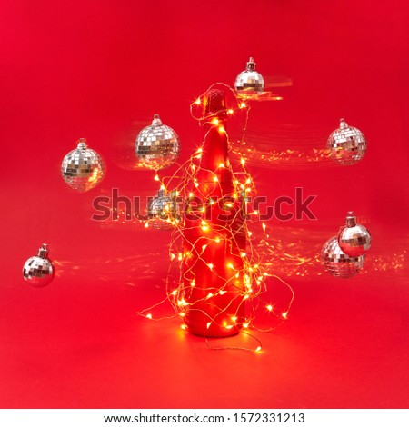 Wine bottle painted red covered garland with lights and flying balls. Stock photo © artjazz