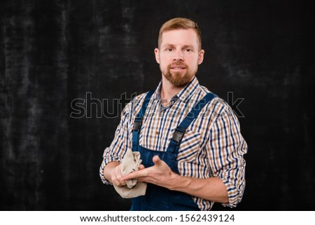 Young bearded mechanic or technician in workwear cleaning hands after work Stock photo © pressmaster