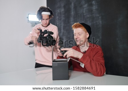 Young cameraman shooting happy male vlogger holding new photocamera Stock photo © pressmaster