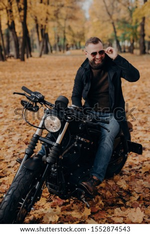 Image of cheerful male motorcyclist smiles joyfully, keeps hand on shades, sits on fast bike, has fu Stock photo © vkstudio