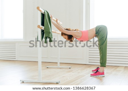 Horizontal shot of motivated woman does push up on ballet bare, warms up before aerobics, wears spor Stock photo © vkstudio