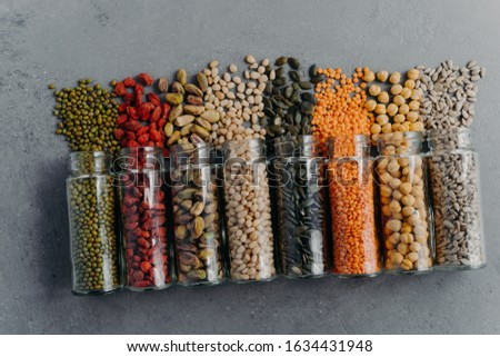 Indoor shot of organic grains, nuts, seeds in transparent glass jars spilled on grey surface. Food p Stock photo © vkstudio