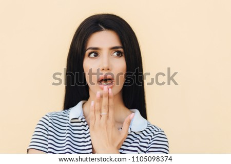 Headshot of scared brunette female covers mouth with hand, looks with fear aside, being frightened t Stock photo © vkstudio