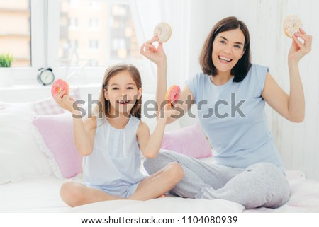 Funny mother and daughter dressed in nightwear, have good mood in morning, hold tasty doughnuts, goi Stock photo © vkstudio