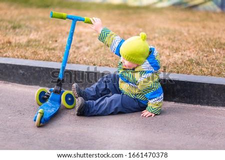 Cute little boy falling off his scooter Stock photo © Len44ik