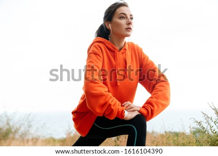 Photo of nice athletic woman using earphones and doing exercise Stock photo © deandrobot