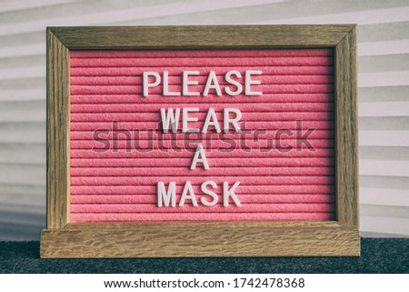 Please wear a mask pink sign at business store entrance message. Obligatory wearing of COVID-19 prot Stock photo © Maridav