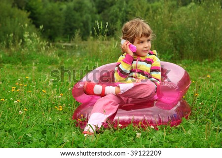 little girl sits talks by toy phone in inflatable armchair on l stock photo © paha_l