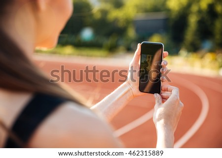 Cropped image of sportswoman making selfie photo on mobile phone Stock photo © deandrobot