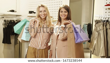 Young woman shopping happily in a fashion store, trying on some  stock photo © lightpoet