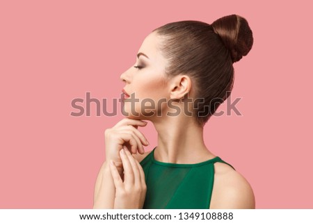 Image of serious woman with brown hair in bun with face upward t Stock photo © deandrobot