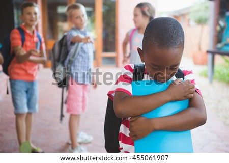 School friends bullying a sad boy in school corridor at school Stock photo © wavebreak_media