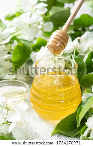 Sweet flower natural honey in a jar and wooden spoon in a puddle of fresh dessert on a gray marble t Stock photo © artjazz