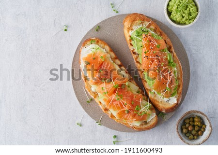 Fresh healthy salmon sandwich with lettuce and cucumber on vintage chopping board on black stone bac Stock photo © DenisMArt