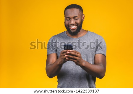 Portrait of teen african american man smiling and holding smartp Stock photo © deandrobot