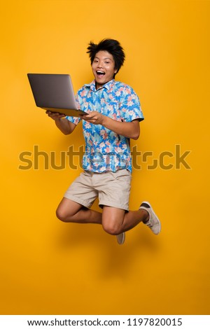 young asian man standing isolated over yellow background using mobile phone drinking coffee stock photo © deandrobot