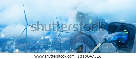 Electric car charging at charger station, cityscape on background Stock photo © MarySan