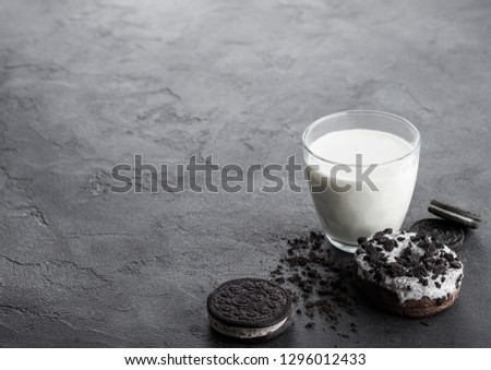 Glass of milk and doughnut with black cookies on stone kitchen table background. Space for text.  Stock photo © DenisMArt
