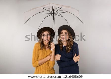 Image of two displeased girls wearing hats standing under umbrel Stock photo © deandrobot