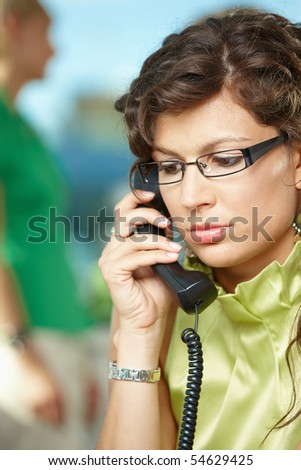 Image of serious woman 20s wearing casual clothing talking on bl Stock photo © deandrobot