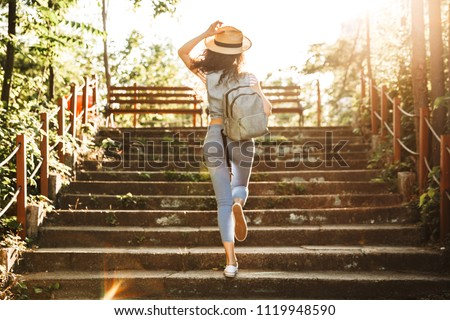 Portrait of joyous woman 20s wearing straw hat rejoicing while h Stock photo © deandrobot