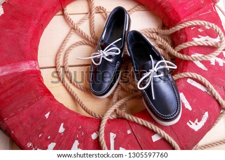 Blue boat shoes on wooden background near red lifebuoy and rope. Stock photo © Illia
