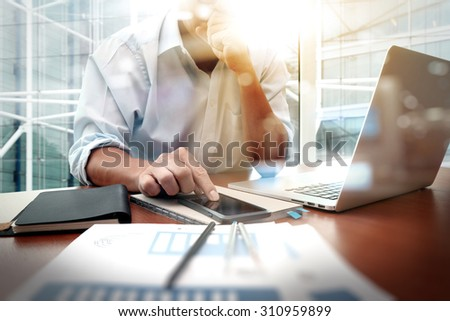 business man working on a laptop tablet and graph data documents Stock photo © snowing