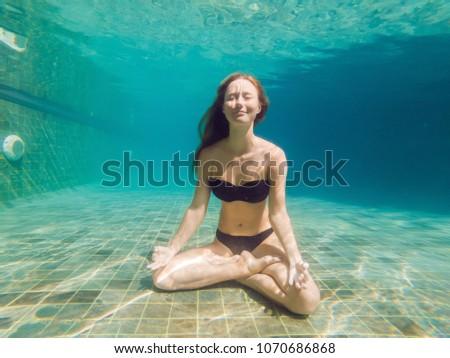 young woman in black bikini in yoga position underwater in diving aquarium, full body shot, front vi Stock photo © galitskaya