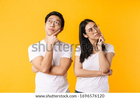 Thinking young asian beautiful woman posing isolated over blue background. Stock photo © deandrobot