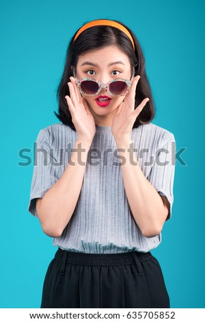 Happy young asian beautiful woman isolated over blue background make winner gesture. Stock photo © deandrobot