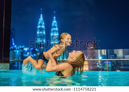 Mother and son in outdoor swimming pool with city view in blue sky Stock photo © galitskaya