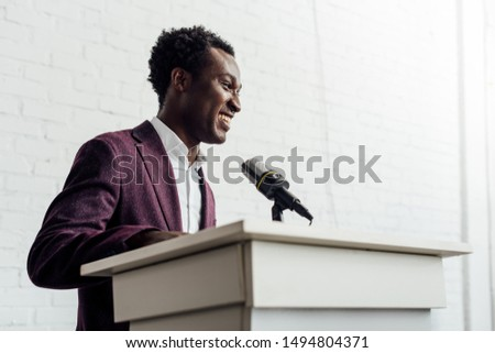 Image of successful man in formal wear speaking on black smartph Stock photo © deandrobot
