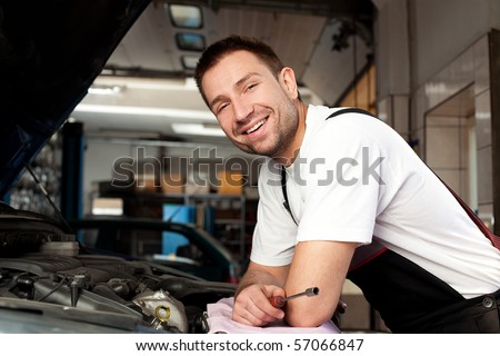 handsome mechanic based on car in auto repair shop with tablet on hand Stock photo © Lopolo