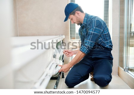 Contemporary technician in workwear installing pipe system by bathtub Stock photo © pressmaster