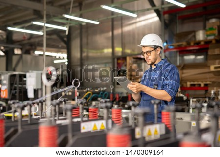 young busy engineer in hardhat and workwear searching for data in the net stock photo © pressmaster