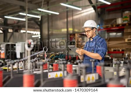 Fiatal elfoglalt mérnök munkavédelmi sisak munkaruha keres Stock fotó © pressmaster