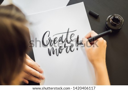 Creat more. Calligrapher Young Woman writes phrase on white paper. Inscribing ornamental decorated l Stock photo © galitskaya