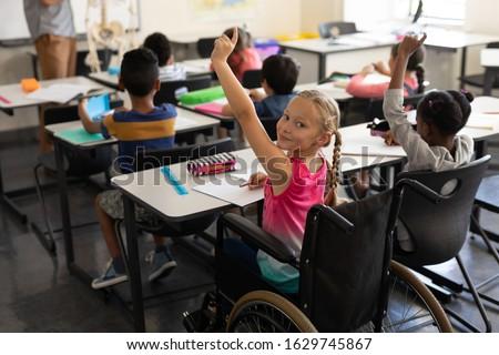 Smiling disable schoolgirl looking at camera and raising hand in classroom of elementary school Stock photo © wavebreak_media