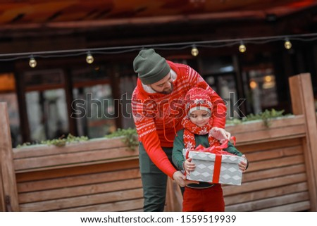 dad with his son in bright holiday clothes posing in front of the camera on the street and holding a stock photo © elenabatkova