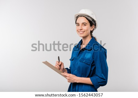 Happy young female mechanic in blue workwear and hardhat holding clipboard Stock photo © pressmaster