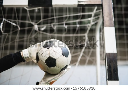 Gloved hands of successful goalkeeper caught soccer ball against net in gate Stock photo © pressmaster