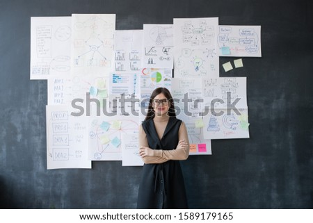 Stock photo: Elegant female economist standing by blackboard with flow charts and diagrams