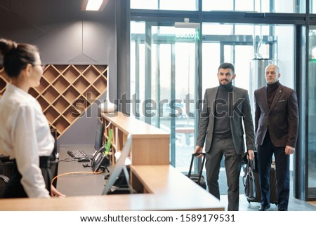Two elegant business travelers with baggage entering hotel lounge Stock photo © pressmaster