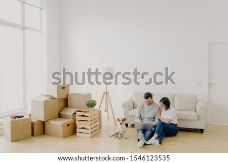 Young relaxed couple move to new home with their favourite pet, sit on floor, surf internet via lapt Stock photo © vkstudio
